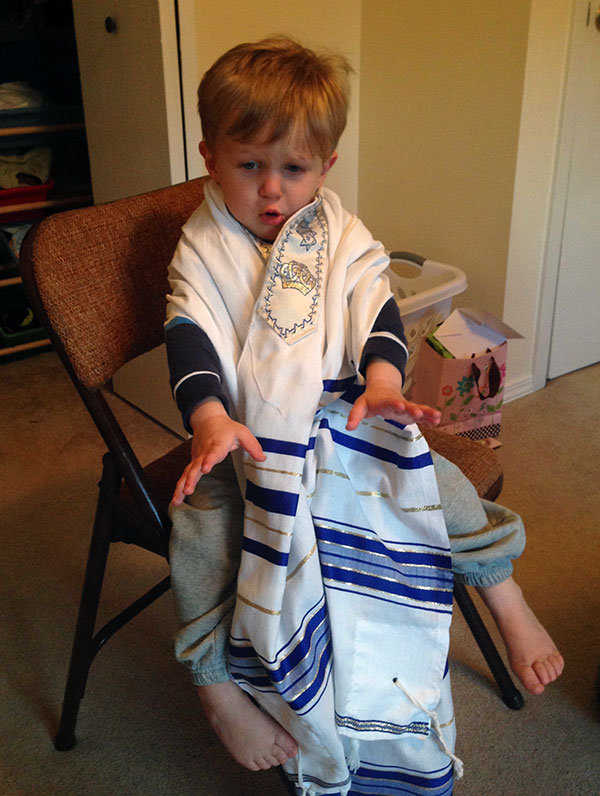 Theo wrapped in Grammie Rita's tallit, and not too keen on it